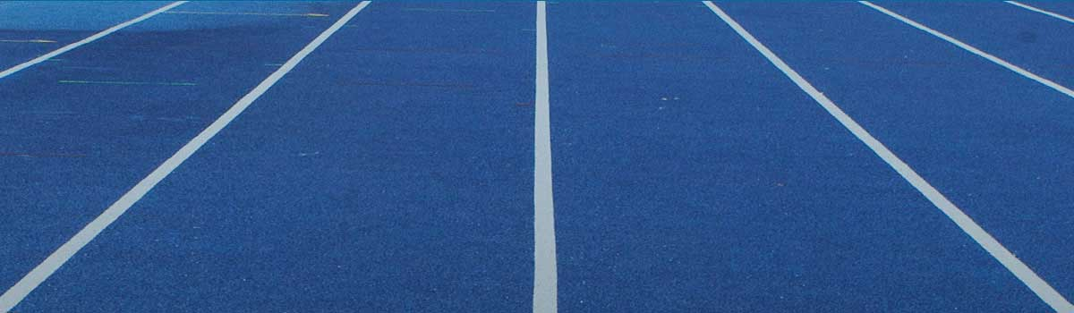 Close up shot of a blue running track with white divider lines